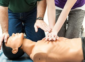 An instructor teaches teen CPR training